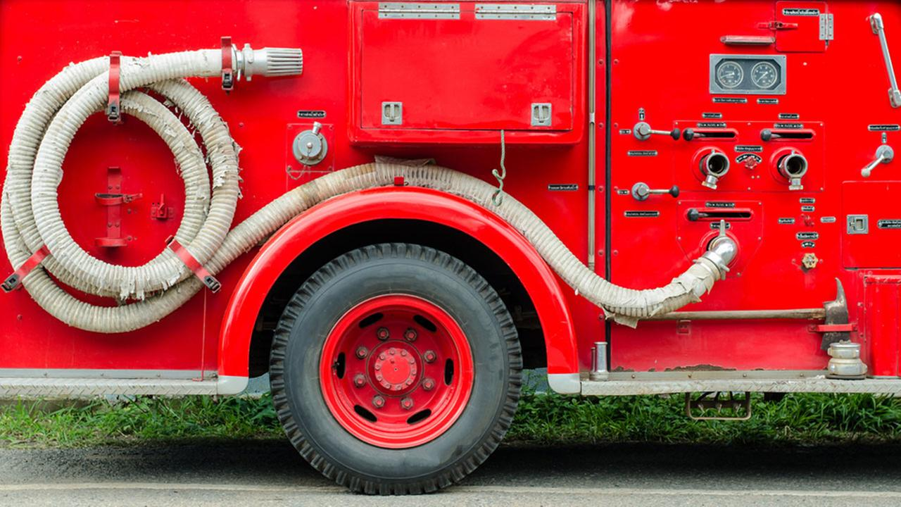 Photo of the side of a red fire truck.