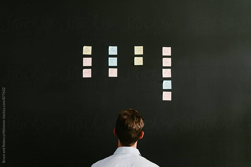 Photo of a man staring at PostIt notes on the wall